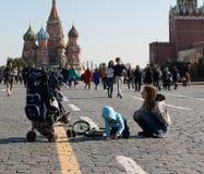 September 2017, Moskva, Ryssland En ung kvinna med ett barn som spelar på den röda fyrkanten nära Kremlväggarna Arkivfoto
