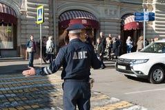 September 2017, Moskva, Ryssland Trafikvakten reglerar övergångsstället nära GUMMIT på röd fyrkant Arkivbild