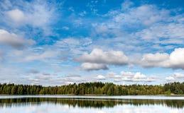September Norge, skogreflexion i en sjö med blå himmel och sockervadden fördunklar i höst royaltyfria foton