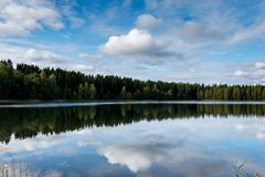 September Norge, skogreflexion i en sjö med blå himmel och sockervadden fördunklar i höst fotografering för bildbyråer