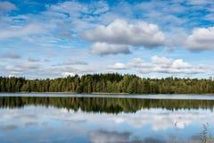 September Norge, skogreflexion i en sjö med blå himmel och sockervadden fördunklar i höst arkivfoto
