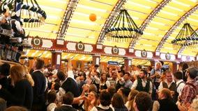17 september, 2017 - Oktoberfest, München, Duitsland: De mensen drinken, zingen, vieren hebben pret in een biertent in Oktoberfes stock video