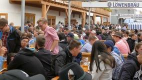 September 17, 2017 - Oktoberfest, Munich, Tyskland: Folket som vilar och att skratta ha gyckel och, sitter dricka öl från enormt lager videofilmer