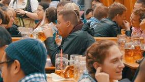 September 17, 2017 - Oktoberfest, Munich, Tyskland: Folket som vilar och att skratta ha gyckel och, sitter dricka öl från enormt arkivfilmer