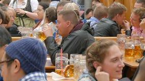 September 17, 2017 - Oktoberfest, Munich, Tyskland: Folket som vilar och att skratta ha gyckel och, sitter dricka öl från enormt stock video