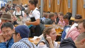 September 17, 2017 - Oktoberfest, Munich, Tyskland: Lotten av folk sitter in birgarten dricka öl från öl rånar arkivfilmer