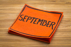 September reminder note. September reminder - handwriting on a sticky note against bamboo wood board Royalty Free Stock Photos