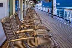 September 15, 2018 - Skagway, AK: Row of cruise ship wooden deck chairs, early morning. September 15, 2018 - Skagway, AK: Row of cruise ship empty wooden royalty free stock image