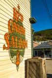 15 september, 2018 - Skagway, AK: Zijaanzicht van de Rode Uizaal en de openbare bak van de sigaretverwijdering van 2de Ave stock foto