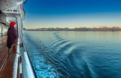 September 14, 2018 - Stephen`s Passage, AK: Woman on cruise viewing mountains. stock image