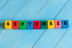 September-teken op kleuren houten kubussen met licht Stock Foto's