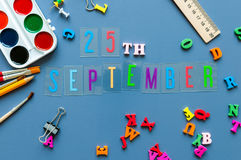 September 25th. Day 25 of month, Back to school concept. Calendar on teacher or student workplace background with school. Supplies on blue table. Autumn time Royalty Free Stock Image