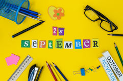 September 25th. Day 25 of month, Back to school concept. Calendar on teacher or student workplace background with school. Supplies on yellow table. Autumn time Royalty Free Stock Images