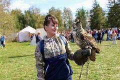 September, 16 2017, Tula, Russia - Historical Festival `Kulikovo Field`: a woman with a glove holds an owl on outstretched hand. Royalty Free Stock Image