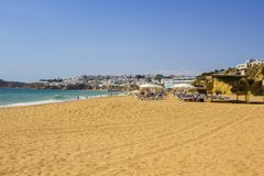 A view along Praia do Inatel beachin Albuferia with sun beds and sand stock photo