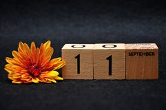 11 September on wooden blocks with an orange daisy. On a black background royalty free stock images