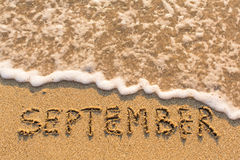 September - Wort gezeichnet auf den Sandstrand mit der weichen Welle Stockfotos