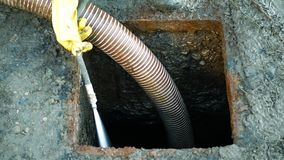 Septic cesspool emptying pumping into pipe tank by suction hose under high pressure. The sump contains pollution sludge