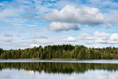 Septiembre Noruega, reflexión del bosque en un lago con el cielo azul y el caramelo de algodón se nubla en otoño Imagen de archivo libre de regalías