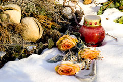 Sepulcher. Orange roses and a red candle lantern on a snowy grave royalty free stock photos