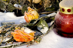 Sepulcher. Orange roses and a red candle lantern on a snowy grave stock photography