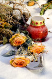 Sepulcher. Orange roses and a red candle lantern on a snowy grave stock images