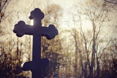 Sepulchral cross at the cemetery. The sepulchral cross at the cemetery in beams setting Stock Photography