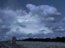 Sepulcro solo por la pista, lápida mortuaria en la naturaleza abierta, parkland Campo con las nubes dramáticas, presentimientos i imagen de archivo