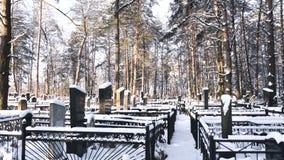Sepulcros en el cristiano nevoso y cementerio o cementerio judío en invierno en bosque metrajes