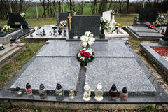 Sepulturas, lápides e crucifixos no cemitério tradicional Velas votivas da lanterna e as flores em pedras do túmulo no cemitério Fotos de Stock