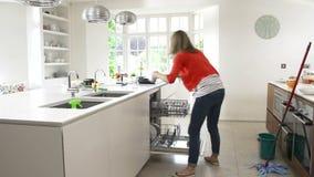 Sequência do lapso de tempo da mulher ocupada que trabalha na cozinha vídeos de arquivo