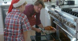 A sequência do movimento lento como o pai toma o peru do Natal fora do forno e dos lugares ele no contador cercado pela família e vídeos de arquivo