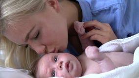 Sequência do movimento lento da mãe que beija a filha do bebê na cama filme