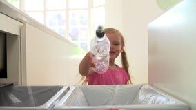 Sequência do movimento lento da menina que recicla o desperdício da cozinha no escaninho vídeos de arquivo
