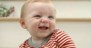 A sequência do movimento lento de pijamas vestindo da criança fêmea bonito sorri na câmera enquanto se senta na escadaria decorad filme