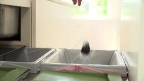 Sequência do movimento lento do homem que recicla o desperdício da cozinha no escaninho video estoque
