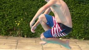 Sequência do movimento lento do menino que salta na piscina video estoque
