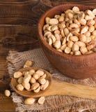 Seque amendoins Roasted em uma bacia e em uma colher de madeira Imagem de Stock