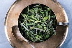 Seque as folhas de chá verdes na colher de madeira sobre a placa marrom Imagem de Stock