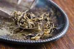 Seque as folhas de chá verdes na colher de madeira sobre a placa marrom Imagens de Stock Royalty Free