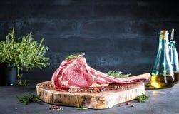Seque el filete de carne de vaca crudo envejecido de la hacha de guerra con los ingredientes para asar a la parrilla imagen de archivo
