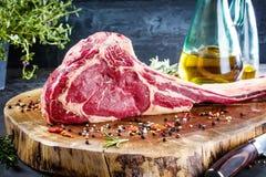Seque el filete de carne de vaca crudo envejecido de la hacha de guerra con los ingredientes para asar a la parrilla fotos de archivo libres de regalías