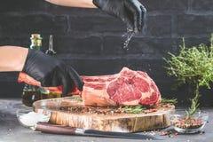 Seque el filete de carne de vaca crudo envejecido de la hacha de guerra con los ingredientes para asar a la parrilla foto de archivo