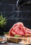 Seque el filete de carne de vaca crudo envejecido de la hacha de guerra con los ingredientes para asar a la parrilla fotografía de archivo libre de regalías