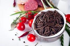 Seque el spiraline italiano de las pastas, tomates de cereza rojos, saussage, aún vida Imagenes de archivo
