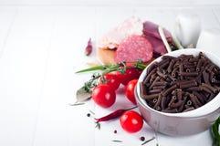 Seque el spiraline italiano de las pastas, tomates de cereza rojos, saussage, aún vida Imágenes de archivo libres de regalías