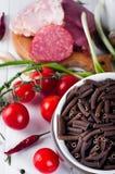 Seque el spiraline italiano de las pastas, tomates de cereza rojos, saussage, aún vida Imagen de archivo libre de regalías