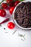 Seque el spiraline italiano de las pastas, tomates de cereza rojos, saussage, aún vida Foto de archivo libre de regalías