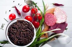 Seque el spiraline italiano de las pastas, tomates de cereza rojos, saussage, aún vida Imagen de archivo
