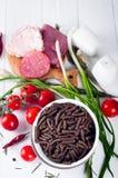 Seque el spiraline italiano de las pastas, tomates de cereza rojos, saussage, aún vida Fotos de archivo libres de regalías